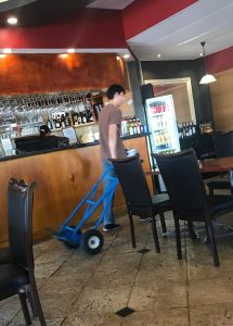 delivery man walking with trolley in restaurant